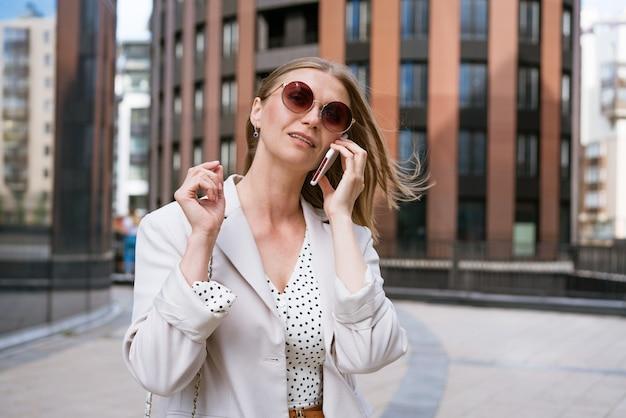 Geschäftsfrau mit telefon in der nähe von büroporträt eines schönen lächelnden mädchens in modischem lichtbüro...