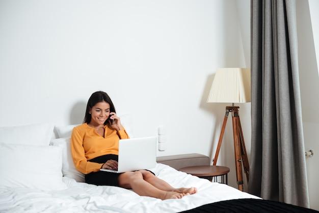 Geschäftsfrau mit telefon und laptop im hotel im bett liegend