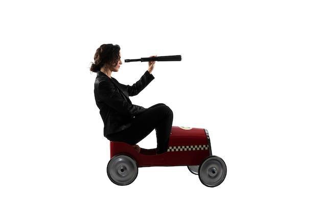 Geschäftsfrau mit teleskop auf einem auto sucht nach neuer geschäftsmöglichkeit, die auf weißer oberfläche isoliert wird