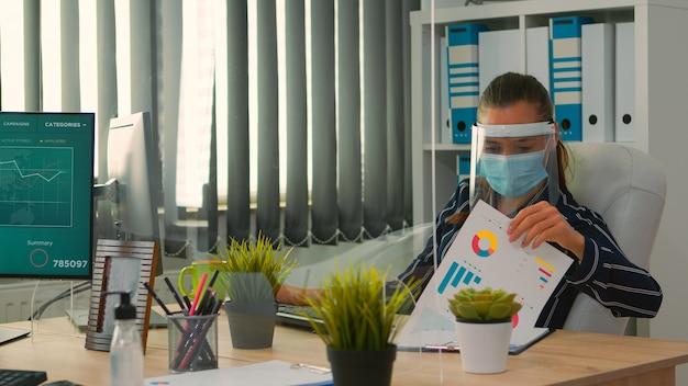 Geschäftsfrau mit visier und schutzmaske, die in einem neuen normalen geschäftsbüro arbeitet. freiberufler, der mit kollegen in finanzunternehmen diskutiert und die soziale distanz während der globalen pandemie respektiert.
