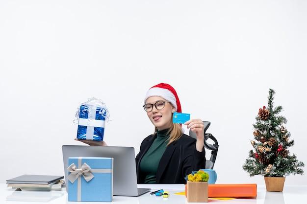 Geschäftsfrau mit weihnachtsmannhut und tragenden brillen, die an einem tisch sitzen, der weihnachtsgeschenk und bankkarte hält und ihre zunge im büro herausstreckt