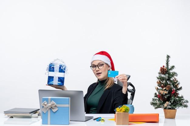 Geschäftsfrau mit weihnachtsmannhut und tragenden brillen, die an einem tisch sitzen, der weihnachtsgeschenk und bankkarte im büro hält