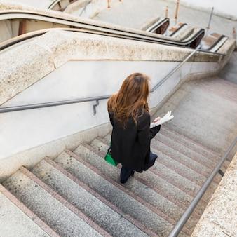 Geschäftsfrau mit zeitung hinunter treppe gehen