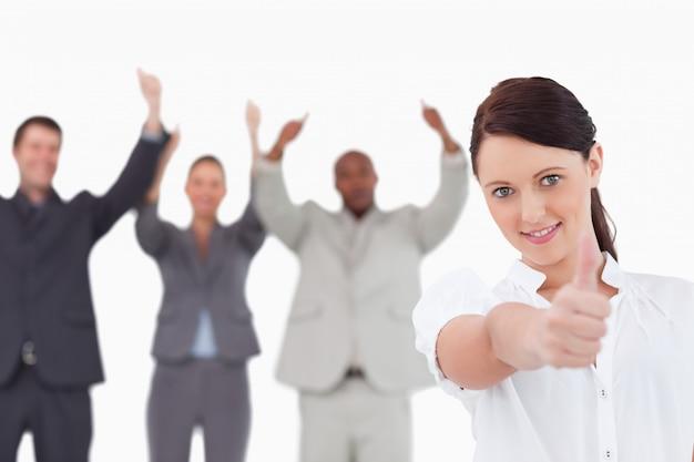 Geschäftsfrau mit zujubelnden kollegen hinter ihr, das daumen aufgibt