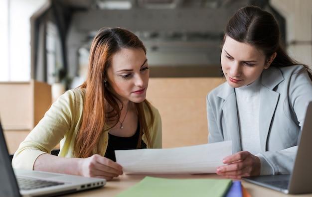 Geschäftsfrau mit zwei jungen, die papier im büro betrachtet