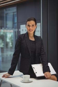 Geschäftsfrau mit zwischenablage, die auf dem schreibtisch im büro sitzt