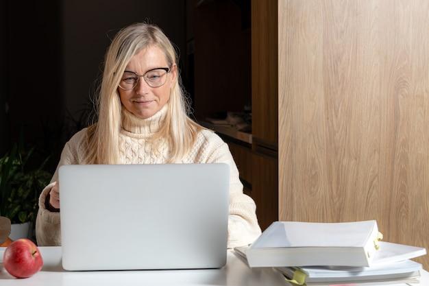 Geschäftsfrau mittleren alters sitzt am schreibtisch und arbeitet mit dokumenten und laptop vom heimbüro