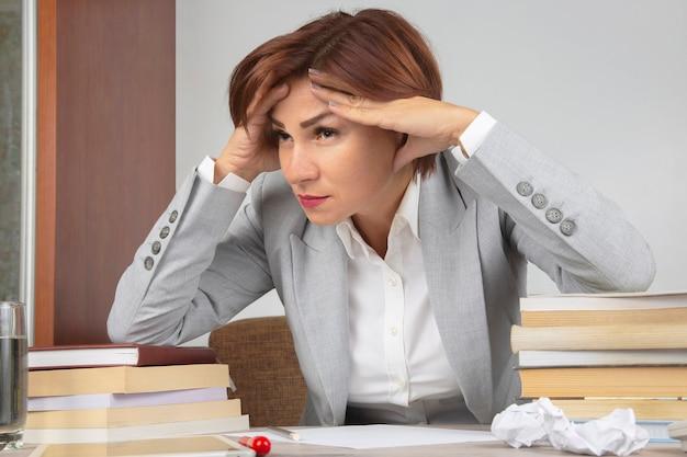 Geschäftsfrau müde im büro und besorgt in emotionen. stress und kopfschmerzen