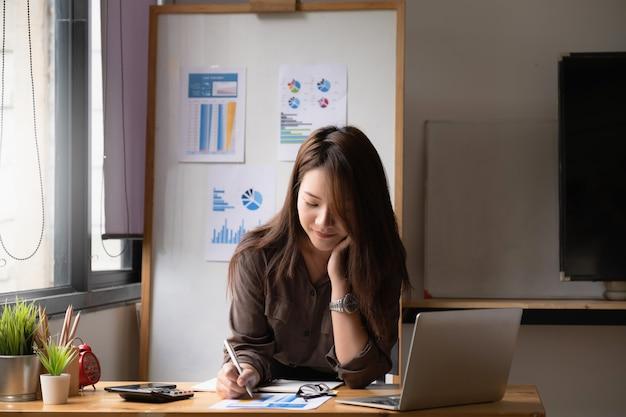 Geschäftsfrau- oder buchhalterhände, die schreibarbeit mit taschenrechner halten
