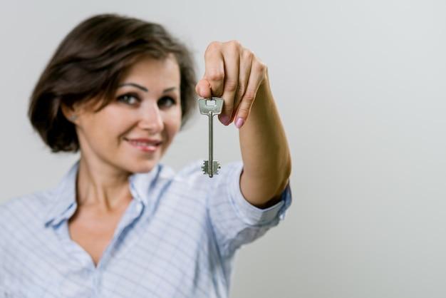 Geschäftsfrau oder immobilienagentur, die schlüssel zeigen