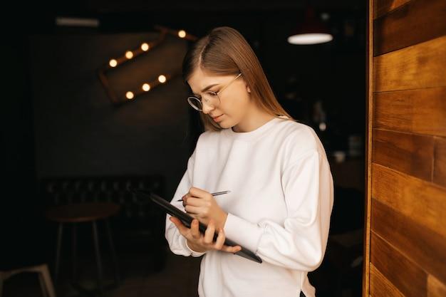 Geschäftsfrau oder student, die notizen aufschreiben, lokalisiert auf schwarzem hintergrund. inspirierte kreative frau, die ideen aufschreibt. arbeitsprozesskonzept.