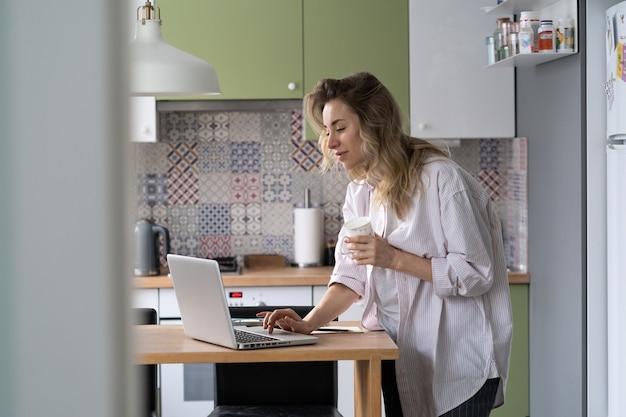 Geschäftsfrau oder telearbeiter arbeiten morgens von zu hause aus und lesen e-mails auf dem laptop, während sie kaffee trinken