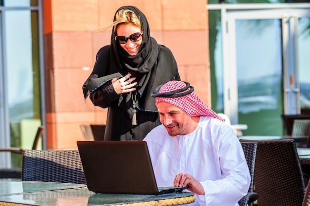 Geschäftsfrau oder verkäuferin, die mit einem arabischen mann arbeitet, der produkte in einer tablette in einem café zeigt