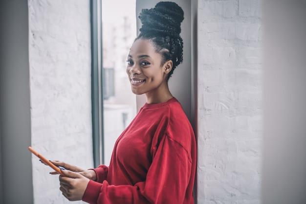 Geschäftsfrau. positive afroamerikanerfrau mit einem laptop, der nahe dem fenster steht