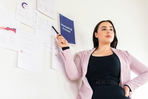 Geschäftsfrau präsentiert eine marketingstrategie an einer weißen wand