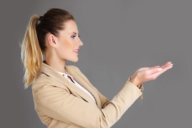 Geschäftsfrau präsentiert etwas auf grauem hintergrund