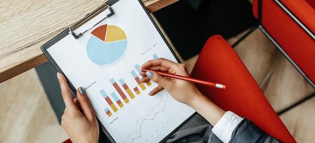 Geschäftsfrau prüft diagramme am arbeitsplatz