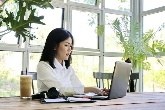 Geschäftsfrau, reizend schöne sonnenbräunehaut asiatische schicke frauenhandarbeit des geschäfts über laptop im glashaus.