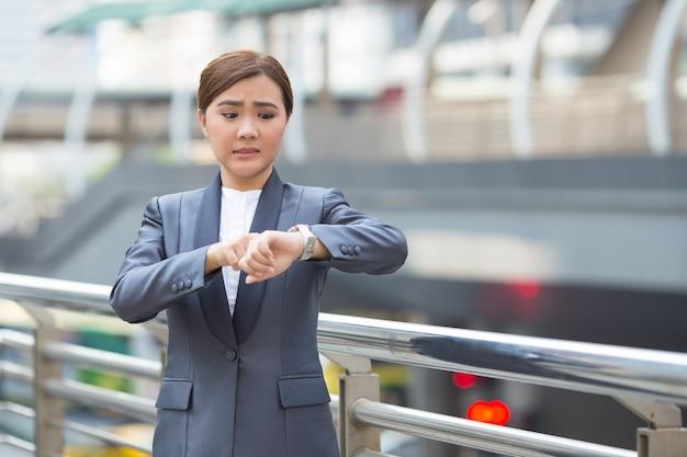 Geschäftsfrau schaut auf die uhr und sie ist spät dran