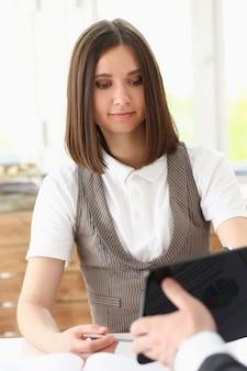 Geschäftsfrau schaut auf tablet-pc im büro