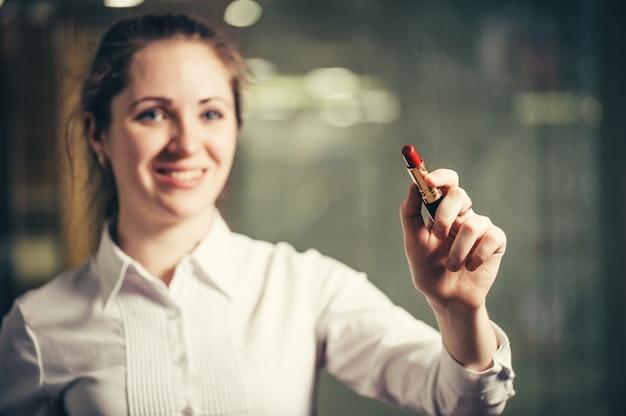 Geschäftsfrau schreibt und zeichnet mit lippenstift auf unsichtbarer virtueller schnittstelle