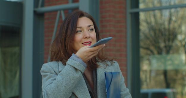 Geschäftsfrau sendet audio auf ihrem smartphone im freien