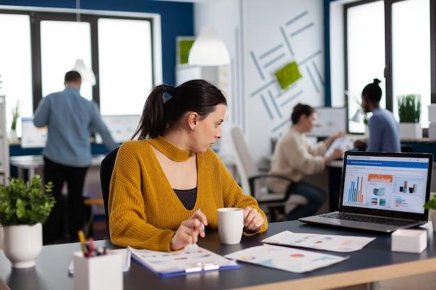 Geschäftsfrau sitzt am schreibtisch im büro und analysiert diagramme auf dem laptop-bildschirm analyzing