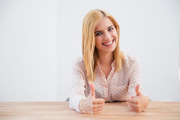 Geschäftsfrau sitzt am tisch mit daumen hoch