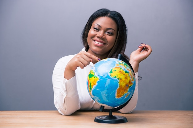 Geschäftsfrau sitzt am tisch mit globus