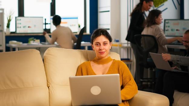Geschäftsfrau sitzt auf der couch mit laptop und lächelt in die kamera, während verschiedene kollegen im hintergrund arbeiten. multiethnische mitarbeiter, die über ein start-up-finanzunternehmen in einem modernen geschäftsbüro sprechen