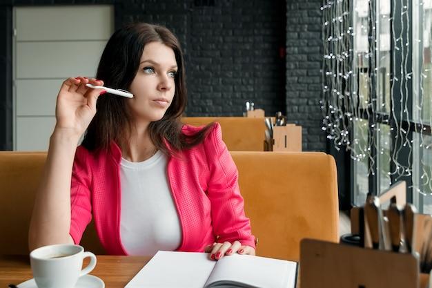 Geschäftsfrau sitzt in einem café und denkt an etwas