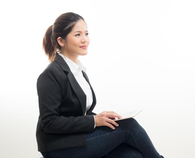 Geschäftsfrau sitzt mit digitalem tablet