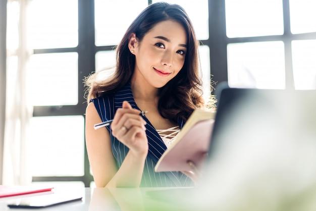 Geschäftsfrau sitzt und arbeitet mit laptop. kreative geschäftsleute planen an ihrem arbeitsplatz auf einem modernen arbeitsboden