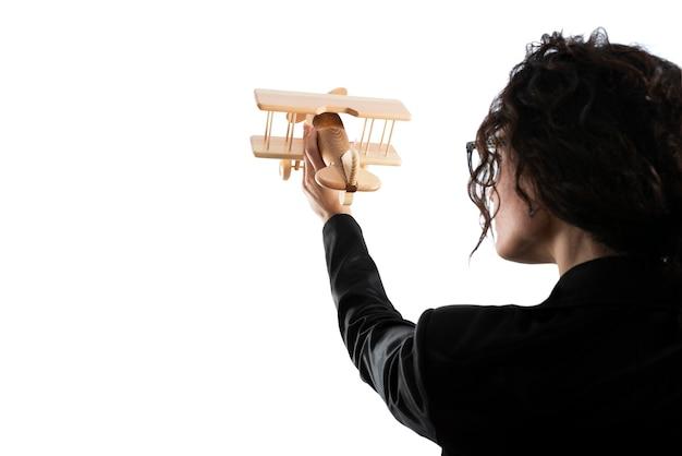Geschäftsfrau spielen mit einem hölzernen spielzeugflugzeug. konzept der unternehmensgründung und des geschäftserfolgs. auf weißem hintergrund isoliert