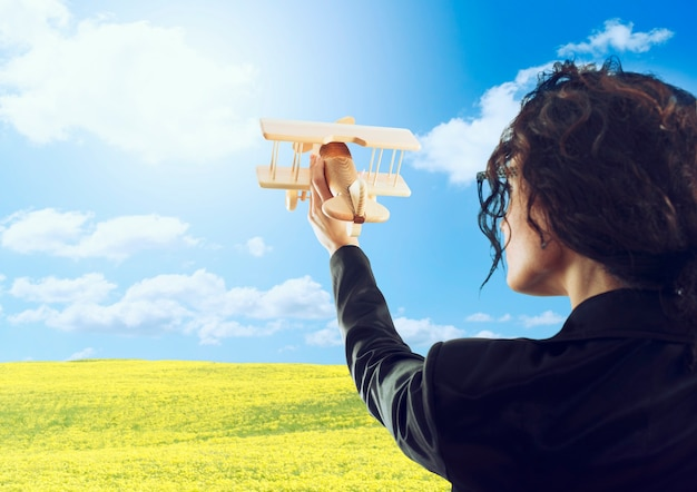 Geschäftsfrau spielen mit einem hölzernen spielzeugflugzeug. konzept der unternehmensgründung und des geschäftserfolgs