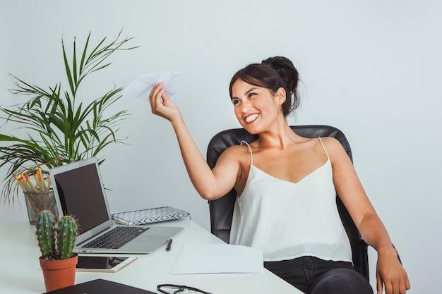 Geschäftsfrau spielt mit einem papier flugzeug