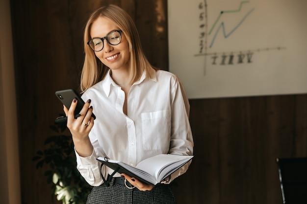 Geschäftsfrau spricht auf einem smartphone. das lächelnde mädchen im büro hält ein telefon in den händen.