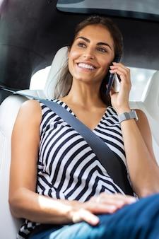Geschäftsfrau spricht. beschäftigte geschäftsfrau, die mit geschäftspartnern telefoniert, während sie im auto sitzt