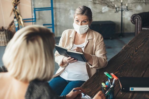 Geschäftsfrau spricht mit dem kunden, der eine maske trägt