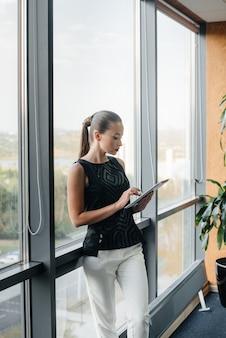 Geschäftsfrau steht im büro in der nähe des fensters und studiert dokumente. wirtschaft, finanzen, anwalt