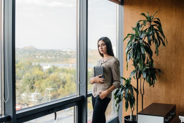 Geschäftsfrau steht im büro in der nähe des fensters und studiert dokumente.
