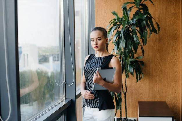 Geschäftsfrau steht im büro in der nähe des fensters. wirtschaft, finanzen, anwalt