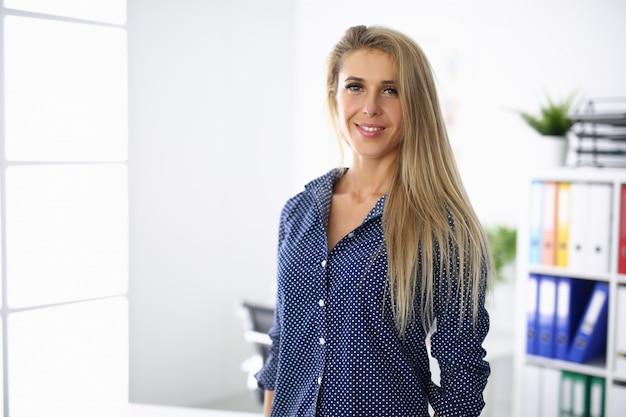 Geschäftsfrau steht im büro und lächelt. geschäftspartnerschaft im kontext des globalen krisenkonzepts