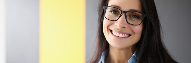 Geschäftsfrau steht im büro und lächelt nahaufnahme