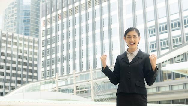 Geschäftsfrau steht mit überzeugtem stadt am im freien