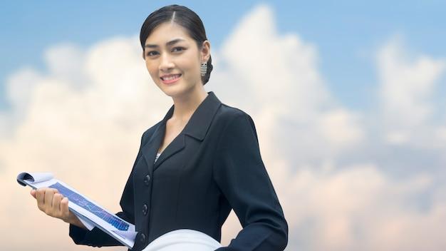 Geschäftsfrau steht mit überzeugtem und bausturzhelm