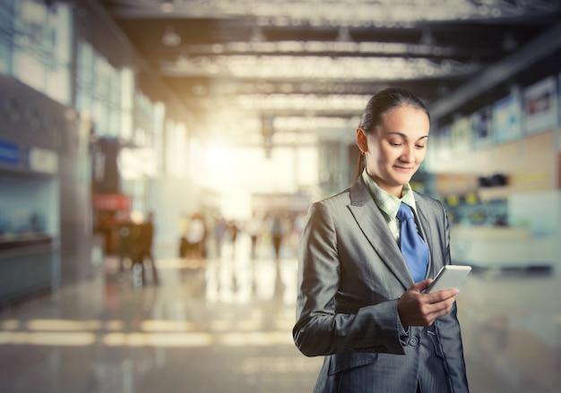 Geschäftsfrau steht und schaut auf ihr telefon