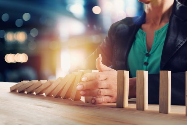 Geschäftsfrau stoppt einen kettensturz wie ein domino-spiel. konzept zur verhinderung von krisen und misserfolgen im geschäftsleben.