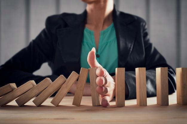 Geschäftsfrau stoppt einen kettensturz wie ein domino-spielzeug. konzept zur verhinderung von krisen und misserfolgen im geschäftsleben