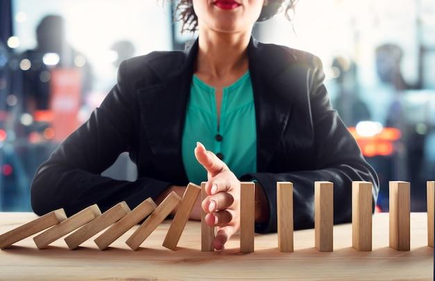 Geschäftsfrau stoppt einen kettensturz wie ein domino-spielzeug.
